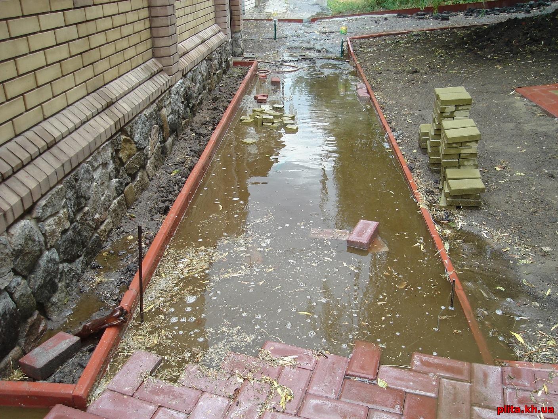 вода уходит по тротуарной плитки